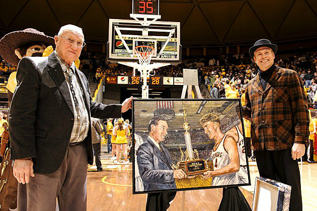 Kenny Sailors poses with a painting from the University of Wyoming's 1943 NCAA Championship. Courtesy of UW Photo Service.
